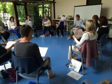 People attending a workshop, sitting on chairs in a circle