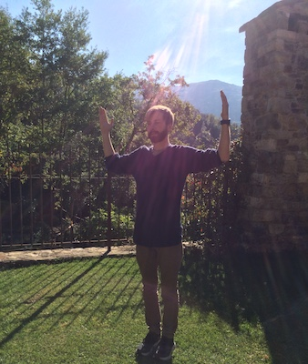 A young man doing Spiritual Portal 5 in the sunlight