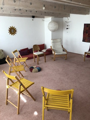 Sideview of a room with yellow chairs and zen decorations
