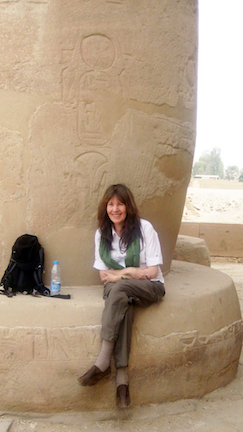 Siska smiling and sitting at the base of a huge pillar in Egypt