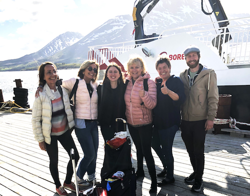 Six people standing on a dock smiling